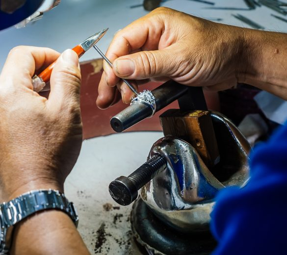 Close up of a goldsmith's hand making silver ring.